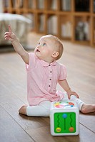 Baby girl sitting on the floor and pointing away with finger