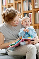 Woman reading a story to her baby from a picture book