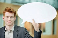 Businessman holding a speech bubble in an office