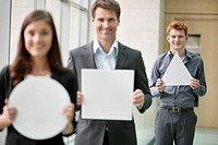 Business executives holding geometrical shaped placards in an office