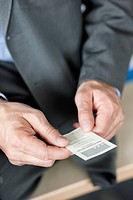 Close_up of a businessman holding a business card