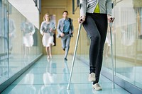 Disabled woman walking with a man and a woman running behind her (thumbnail)