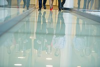 Reflection of business executives on the glassy floor