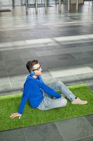 Businessman relaxing on grass and listening to music in an office lobby