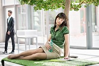 Businesswoman relaxing on grass mat