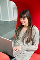 Businesswoman using a laptop and smiling in an office