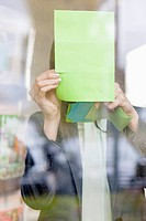 Businesswoman sticking memo notes on glass in an office