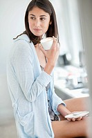 Woman drinking coffee in pajamas