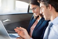 Businessman and businesswoman using laptop in back seat of car