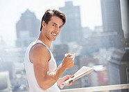 Portrait of smiling man drinking coffee and reading newspaper on urban balcony (thumbnail)