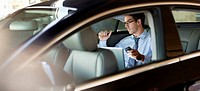 Businessman holding cell phone and using laptop in back seat of car