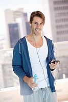 Portrait of smiling man holding water bottle and listening to mp3 player on urban balcony