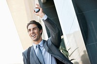 Smiling businessman holding cell phone and waving