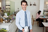 Portrait of smiling businessman holding take out coffee cups in cafe