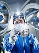 Portrait of surgeon holding one hundred dollar bill under surgical lights