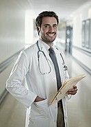 Portrait of confident doctor holding medical record in hospital corridor