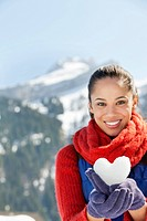 Portrait of smiling woman holding heart-shape snowball (thumbnail)