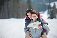 Man piggybacking woman in snow