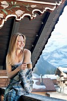 Portrait of smiling woman drinking coffee on cabin porch