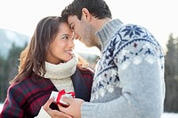 Smiling couple face to face with Christmas gift (thumbnail)