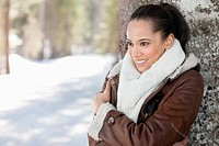 Smiling woman leaning against tree trunk in snow (thumbnail)