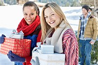 Portrait of smiling friends with Christmas gifts in snow