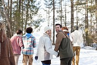 Portrait of smiling couple holding hands and walking with friends in snowy woods
