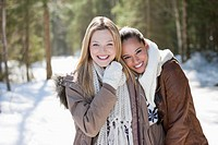 Portrait of smiling friends hugging in snowy woods