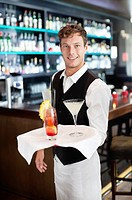 Portrait of smiling bartender holding tray with cocktails in bar