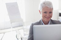 Portrait of smiling businesswoman working at laptop