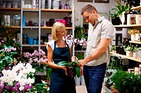 Attractive young florist recommending an orchid to a flower store client