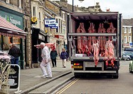 Unloading pig and lamb carcases from lorry to butchers shop, Barnard Castle, Teesdale, County Durham, England, july