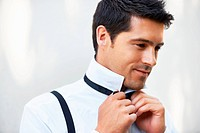 Handsome groom thinking and putting on his bowtie while getting dressed for his wedding