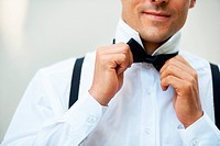Young groom tying his black bowtie around his collar getting dressed for his wedding day