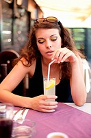 Young woman drinking soda in a restaurant