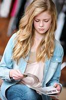 Teenage Girl With Long Blond Hair And Blue Eyes Reading A Magazine, Troutdale Oregon United States Of America
