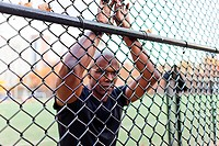 Man leaning on chain link fence