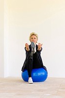 Mature woman sitting on fitness ball with arms out and one leg up