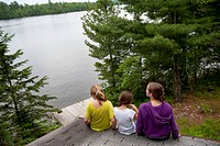 Three girls sitting on the edge of a roof by a lake, lake of the woods ontario canada