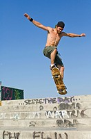 A Young Man Jumps Off The Steps On A Skateboard