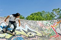 A Young Man Skateboarding On A Graffiti Filled Skatepark Slope