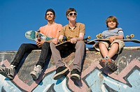 Three Young Men Sitting On The Edge Of A Skatepark With Their Skateboards