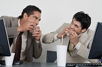 Businessmen eating fast food at desk in office