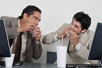 Businessmen eating fast food at desk in office