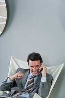 Mature businessman using cell phone, making fist and smiling
