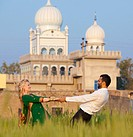 A mixed race couple holding hands in a field with a temple in the background, ludhiana punjab india