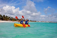 Two women in lifejackets paddling in a yellow boat, punta cana la altagracia dominican republic