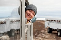 A young woman looks out the window of a tundra vehicle on a polar bear expedition, churchill manitoba canada