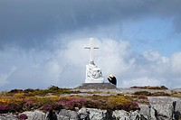 A woman kneels in prayer at a white cross and statue at sheep´s head near ahakista, county cork ireland