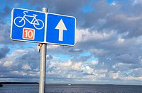 Bicycle path sign nr ten near lake and cloudy sky.
